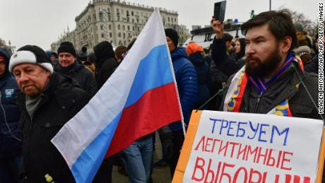 "One protester in Moscow brandishes a placard saying: ""Demand lawful election."""