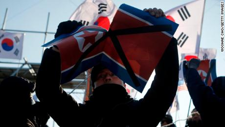 A protester rips up the North Korean flag outside Sunday's hockey match.