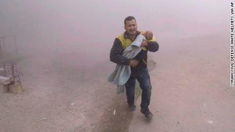 A photo provided by the Syrian Civil Defense group shows what it says is one of its paramedics fleeing with his wounded son from the scene of an airstrike near Damascus on Tuesday.