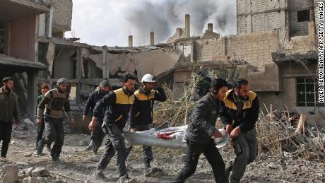 White Helmets members evacuate a victim of an airstrike Thursday in the rebel-held enclave of Hazeh.