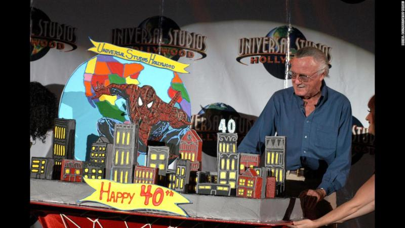 Lee poses by a cake celebrating Spider-Man's 40th anniversary.