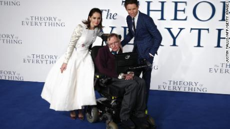 """British actors Felicity Jones and Eddie Redmayne pose with Stephen Hawking at the UK premiere of the """"The Theory of Everything"""" in London on December 9, 2014."""