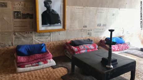 """A photo of a youthful Xi as well as old newspapers adorn the wall above his old shared bed in a """"cave house."""""""