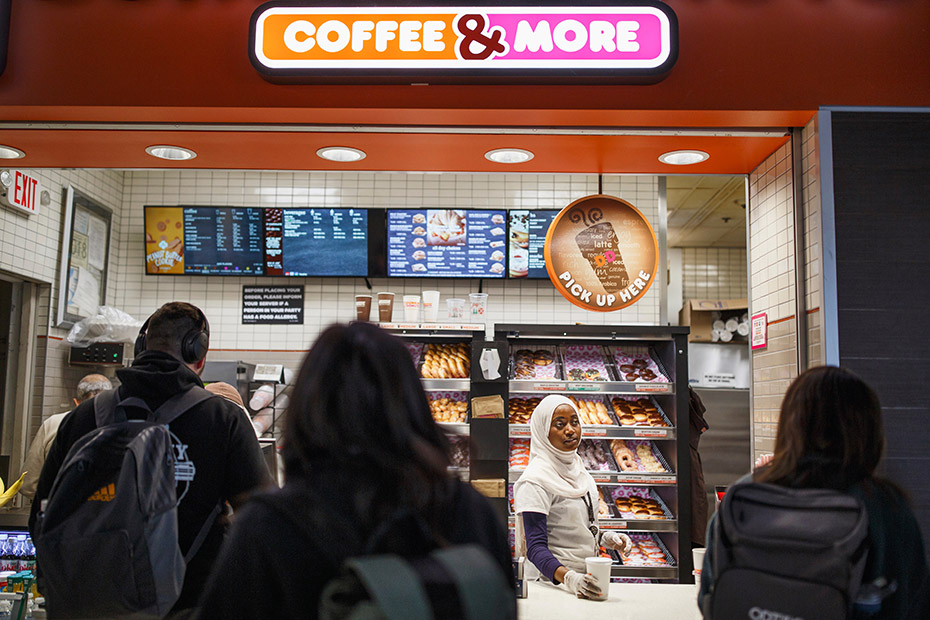 Batulo serves drinks to customers at the airport Dunkin' Donuts. Occasionally, she helps lost passengers find their way. (Melissa Golden/Redux for CNN)