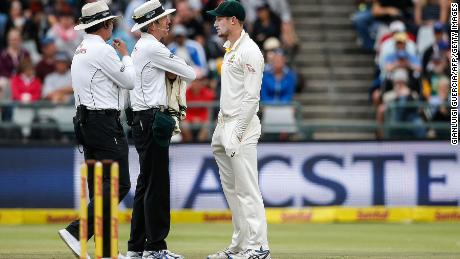 Australian fielder Cameron Bancroft (R) is questioned by Umpires Richard Illingworth and Nigel Llong during the third day of the third Test cricket match between South Africa and Australia on March 24, 2018 in Cape Town.