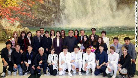 Kim Jong Un and his wife Ri Sol Ju pose with South Korea's Culture, Sports and Tourism Minister Do Jong-whan and South Korean musicians in this image released by KCNA.