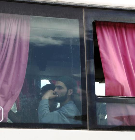 A Syrian man is seen aboard a bus carrying fighters and their families from their former rebel bastion of Douma as they arrive at the Syrian government-held side of the Wafideen checkpoint on the outskirts of Damascus.