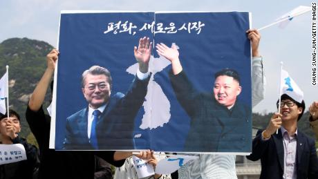 South Koreans hold up placards during a rally welcoming the planned Inter Korean Summit in front of Presidential Blue House on April 26.