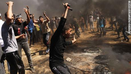 Palestinians rush to the border fence with Israel as mass demonstrations at the fence continue on May 14, 2018 in Gaza.