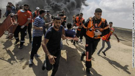 Medical units carry away a wounded Palestinian shot by Israeli forces during a protest on the border fence separating Israel and Gaza on May 14, 2018.