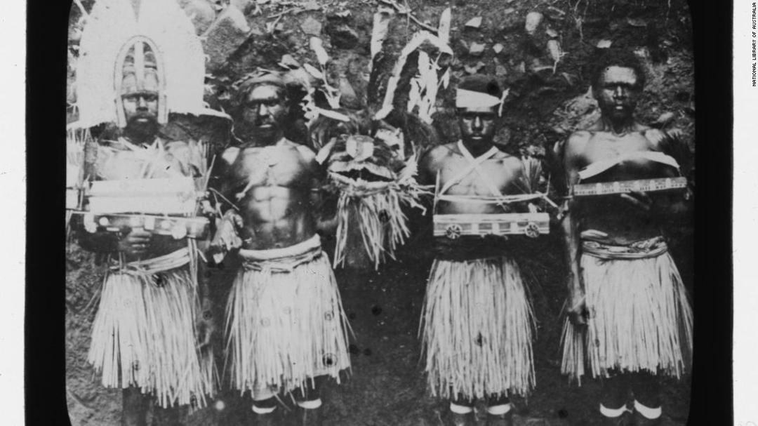 Four Torres Strait men in traditional dress and holding ceremonial objects on Hammond Island in 1905, photographed by Otto Watson.