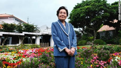 Yoshiko Shimabukuro stands in the garden area of the Himeyuri Peace Museum, which she helped establish.