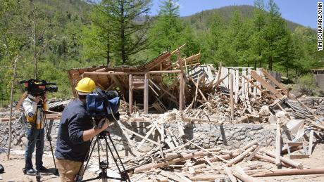 Journalists film the Punggye-ri nuclear site after the tunnels are detonated.