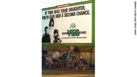 Irish women push strollers under a government-sponsored poster in Dublin, 1995.