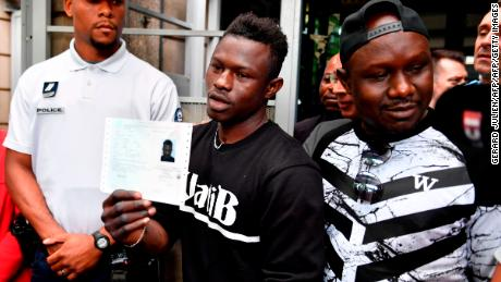 Flanked by his older brother, Gassama holds his temporary residence permit after receiving it Tuesday.