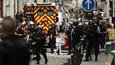 A woman and young girl are evacuated by police Tuesday during a hostage situation in Paris.