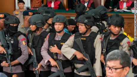 Indonesian anti-terror police officers escort Abdurrahman in court.