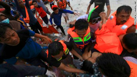 Rescuers remove a passenger from the sinking  KM Lestari Maju ferry.