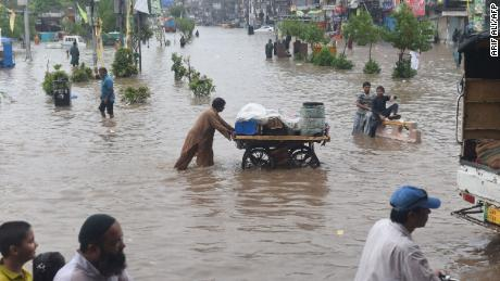 Pakistani residents cross a flooded street in Lahore after monsoon rains on July 3, 2018.