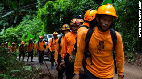 Men from the Department of Disaster Prevention and Mitigation arrive to the cave entrance on July 6, in Chiang Rai, Thailand.