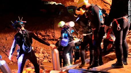In this undated photo released by Royal Thai Navy on Saturday, July 7, 2018, Thai rescue team members walk inside the cave.