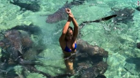 Katarina Zarutskie covers the shark bite with hand as she rushes out of the water