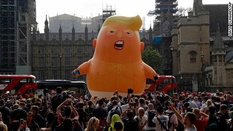 The blimp was inflated in front of the House of Commons as crowds look on.