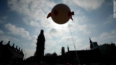 """The """"Trump Baby"""" is seen against the backdrop of the scaffolded Houses of Parliament and Big Ben in London."""