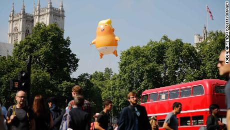 """Pedestrians walk past as a giant """"Trump Baby"""" balloon floats near the towers of Westminster Abbey."""