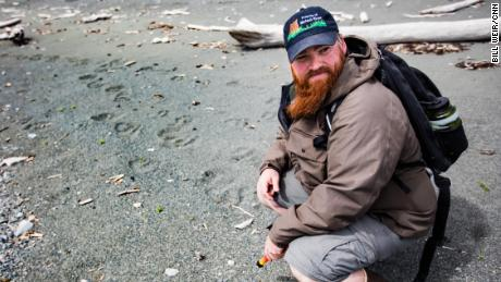 Drew Hamilton, from Friends of McNeil River, finds bear tracks on Amakdedori Beach.