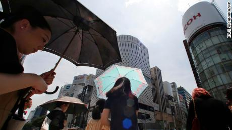 People shade themselves from the heat of the sun with umbrellas in Tokyo on July 23, 2018.