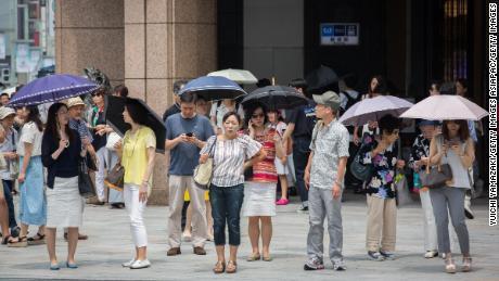 Les gens utilisent des parasols pour tenter d'échapper à la chaleur le 22 juillet 2018 à Ginza Tokyo, au Japon.