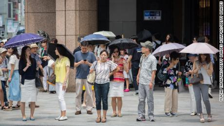 People use parasols to try and escape the heat on July 22, 2018 in Ginza Tokyo, Japan.