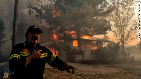 A firefighter works to quell the blaze in Kineta, west of Athens Monday.