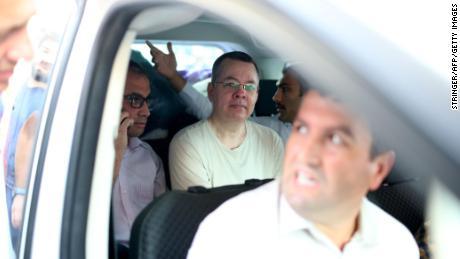 Andrew Brunson, au centre, est aperçu à l'intérieur d'une voiture escortée par des polici ers turcs en civil alors qu'il arrive chez lui à Izmir le 25 juillet.