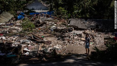 A man stands near the ruins of their houses at a collapsed house following an earthquake on August 8, 2018 in Lombok Island, Indonesia.