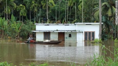 An Indian man steers his boat past houses immersed in flood waters in Kochi, in Kerala state, on Friday.