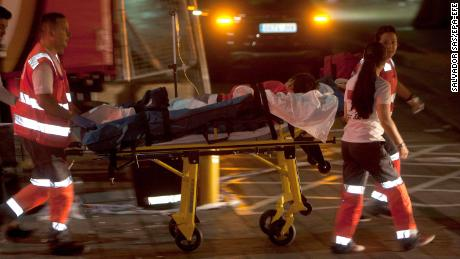 Red Cross paramedics transport an injured person to the hospital after the platform collapsed late Sunday night.