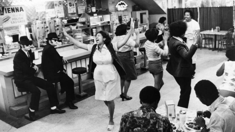 "Dan Aykroyd (far left), John Belushi (second left), Aretha Franklin (center) and Matt ""Guitar"" Murphy (back right) in a scene from the 1980 film, ""The Blues Brothers."""