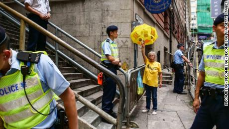 A counter-protester raises a yellow umbrella decorated with the Union flag as police officers stand guard during a demonstration by pro-China groups outside the Foreign Correspondents' Club in Hong Kong.