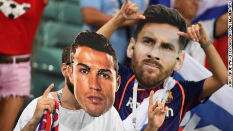 Fans wear Ronaldo and Messi masks during the Russia 2018 World Cup.