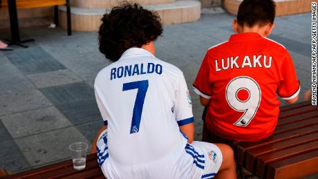 Boys wearing Real Madrid's and Manchester United jerseys sit on a bench in Skopje, Macedonia.