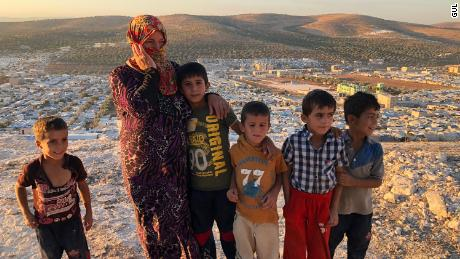 """Vaciha Turki-Al Omar, 30, has been in Idlib for seven months. She stands on the hill overlooking the sprawling refugee camp with her kids. """"We can try to fight, but the kids are our weakness so we must run away,"""" she says."""