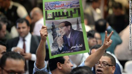 A man carries a newspaper bearing the portrait of President Sisi in Cairo on April 2.