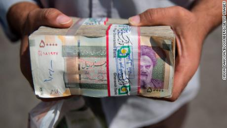A currency trader holds a bundle of Iranian rial banknotes outside a bazaar in Tehran.