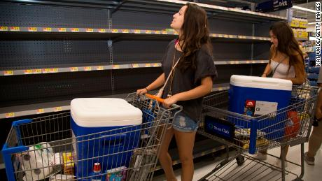 Two University of Hawaii at Manoa students browse the aisles of a Walmart looking for food and supplies ahead of Hurricane Lane.