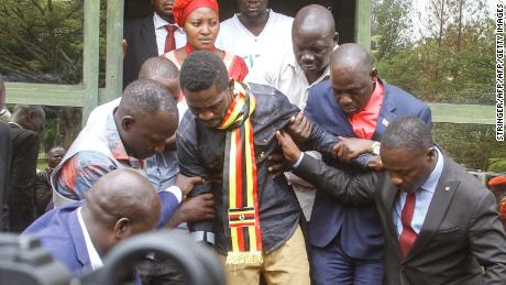 Ugandan politician Robert Kyagulanyi, known as Bobi Wine, center, is helped down stairs before appearing at the general court martial in Gulu, northern Uganda on August 23, 2018.
