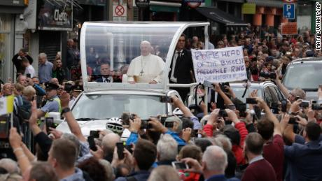 Pope Francis passes a protest banner after visiting St Mary's Pro-Cathedral in Dublin on Saturday.