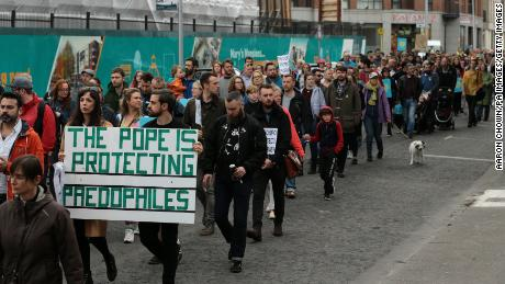 """Ailbhe O'Rourke and Fionn Dally hold a sign reading: """"The Pope is protecting paedophiles"""" in protest over clerical sex abuse."""