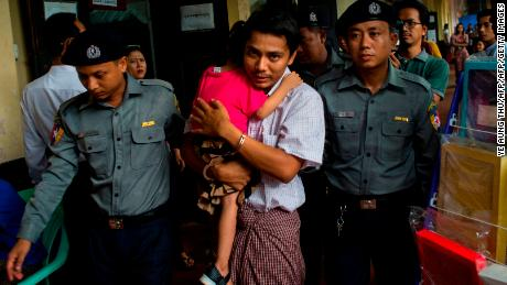 Detained Myanmar journalist Kyaw Soe Oo carries his daughter as he is escorted by police to a courtroom for his trial in Yangon last month.